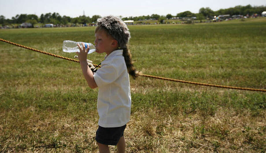 Rylan Smith, 4 wears his coon-skin cap as he takes a sip of water while he waits to see the reenactment on the grounds of the San Jacinto Battleground. Photo: Karen Warren, Houston Chronicle
