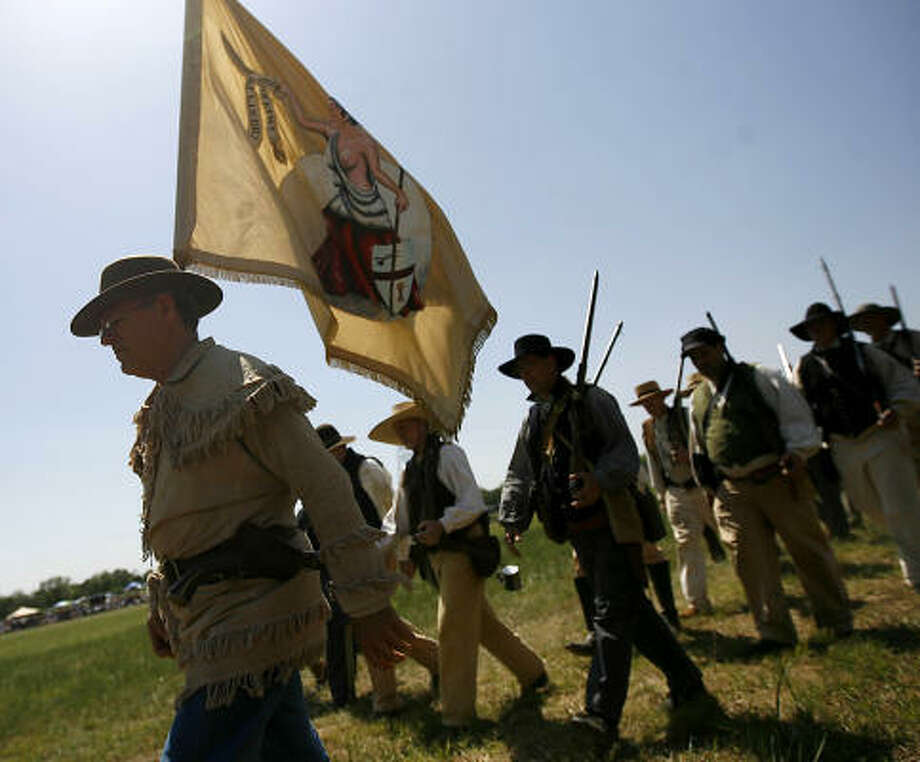 Re-enactors dressed as members of the Texian Army walk on the grounds of the San Jacinto Battleground. Photo: Karen Warren, Houston Chronicle