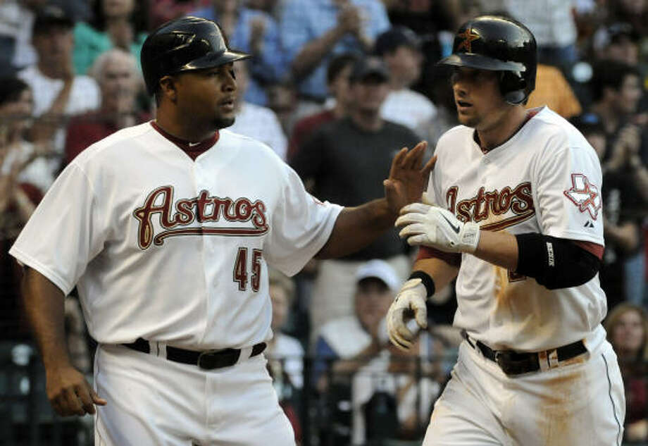 Astros' Carlos Lee (45) greets teammate Chris Johnson at home after Johnson's two-run home run in the fourth inning. Photo: Pat Sullivan, AP