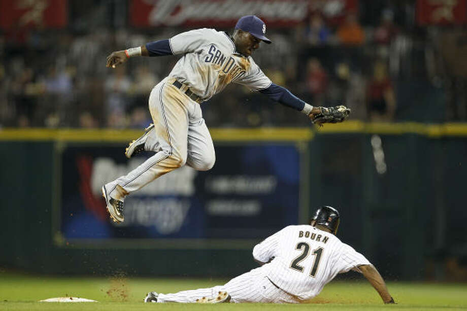 Michael Bourn (21) slides safely into second base on a steal as Padres second baseman Orlando Hudson jumps in the air to catch the ball. Photo: Michael Paulsen, Chronicle
