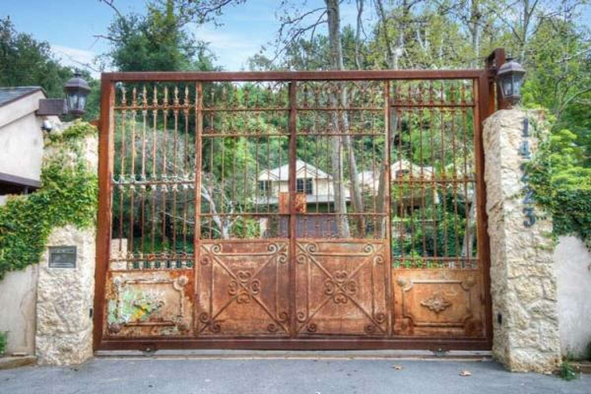 A rustic iron gate greets visitors to the property. The woodsy compound features a French-inspired home that has eight bedrooms, 8.5 baths and 8,400 square feet, as well as a studio, swimming pool, putting green, year-round creek, barn, corral and a guest home.