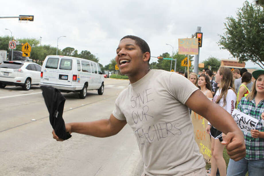 Paul Leake, an 11th-grader at Cinco Ranch High School, yells at passing cars to honk their horns in support of teachers staying on the job. Photo: Alan Warren, Chronicle