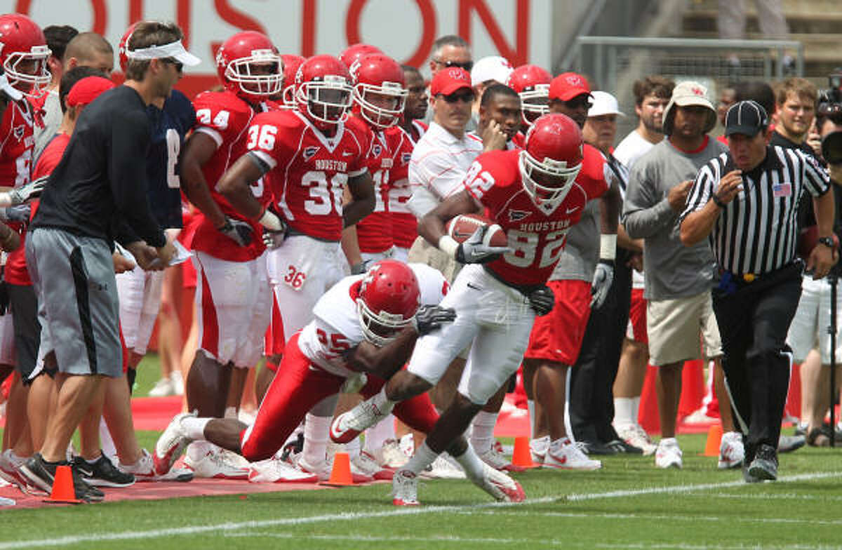 The University of Houston's White team's Alex Tillman center left, pulls the Red team's Chance Blackmon center right, out of bounds during the second quarter of the Red & White spring football game at Robertson Stadium on Saturday.