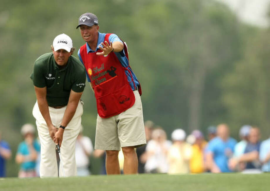 "Phil Mickelson (left) gets putting advice from caddie Jim ""Bones"" McKay on the No. 12 green. Photo: ERIC CHRISTIAN SMITH, FREELANCE"