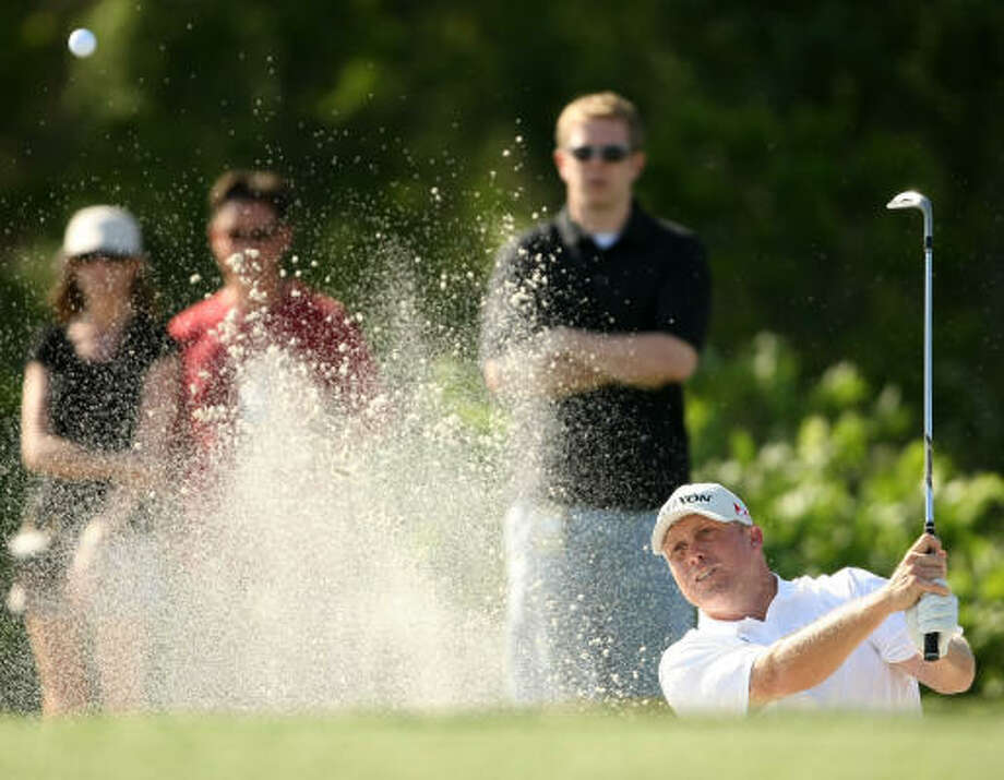 John Rollins blasts out of a greenside bunker on No. 15. Photo: ERIC CHRISTIAN SMITH, FOR THE CHRONICLE
