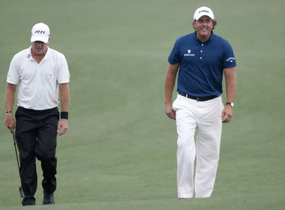 Phil Mickelson (right) walks up to the No. 18 green with playing partner Scott Verplank during the final round of the Shell Houston Open at Red Stone Golf Club Sunday. Mickelson brought home the victory by three shots. Photo: Cody Duty, Houston Chronicle
