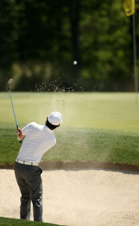 Anthony Kim blasts out of a greenside bunker on No. 8. Photo: ERIC CHRISTIAN SMITH, For The Chronicle