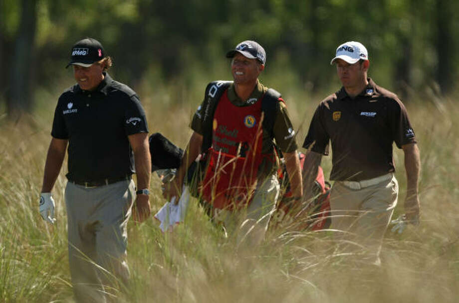 "Phil Mickelson (left), Mickelson's caddie Jim ""Bones"" McKay and Lee Westwood walk to the 12th fairway during the first round of the Shell Houston Open, Thursday at Redstone Golf Club in Humble. Photo: ERIC CHRISTIAN SMITH, For The Chronicle"