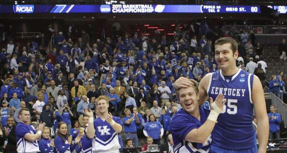 Kentucky forward Josh Harrellson (55) is congratulated by a cheerleader as he walks off the court after beating Ohio State.