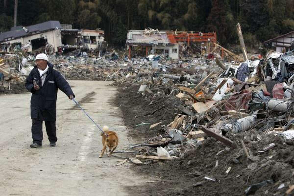 Walking past rubble from destroyed buildings March 19 in Rikuzentakata, Japan.