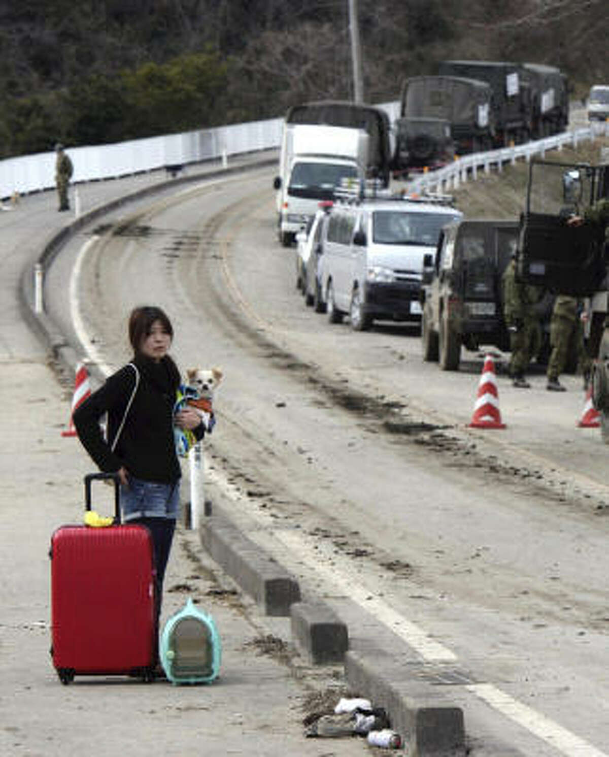 A woman with her dog and belongings leaves Higashimatsushima, Miyagi Prefecture, northern Japan, March 14.