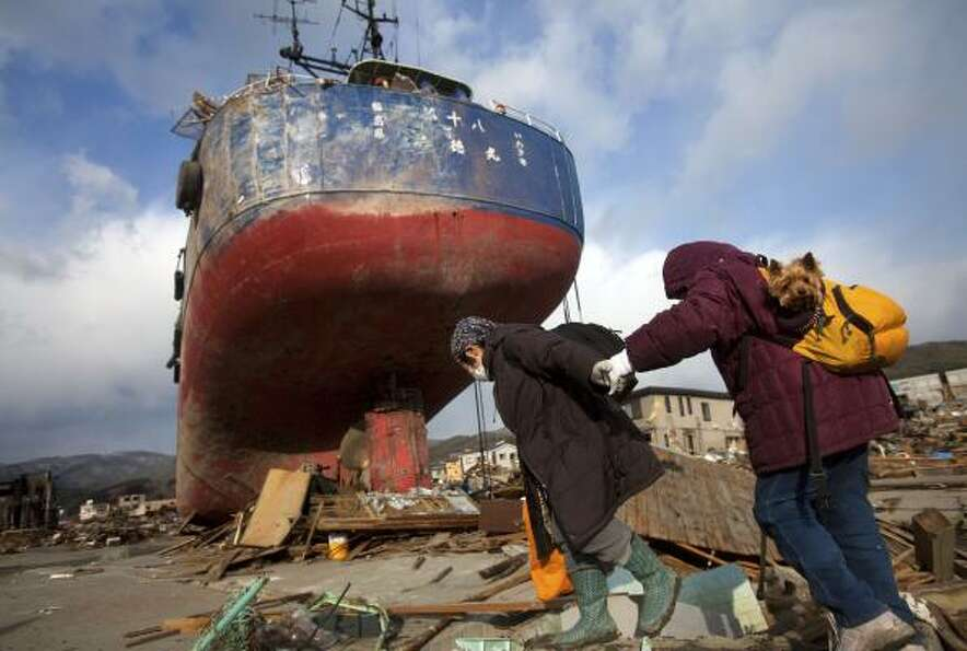 Japanese women and a pet dog pass by a ship that was washed into their neighborhood by the tsunami a