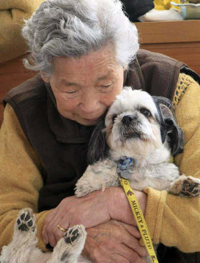 Tami Akanuma, 83, holds her Shih-tzu Babu at an evacuation center in Miyako, Japan.  Akanuma's home was about 220 yards from a coast. When the tsunami alert was issued, Babu dashed out the door toward a hill and Akanuma followed the dog to safety. Babu celebrated her 12th birthday on March 23. Photo: Tetsuya Kikumasa, AP