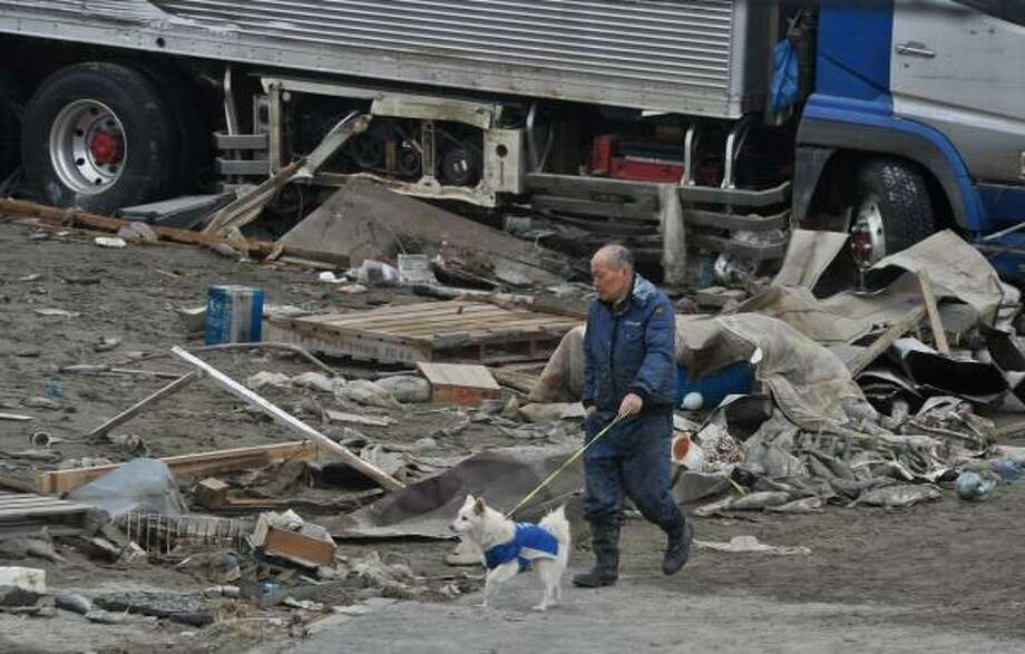 Walking amid the rubble of Ishinomaki, Japan, on March 21. Photo: NICHOLAS KAMM, AFP/Getty Images