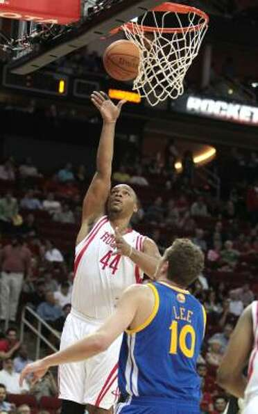 Rockets center Chuck Hayes, left, puts up a shot as Warriors forward David Lee (10) watches the play