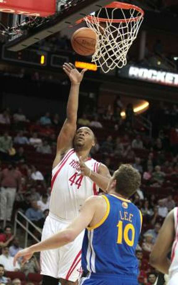 Rockets center Chuck Hayes, left, puts up a shot as Warriors forward David Lee (10) watches the play. Photo: Billy Smith II, Chronicle