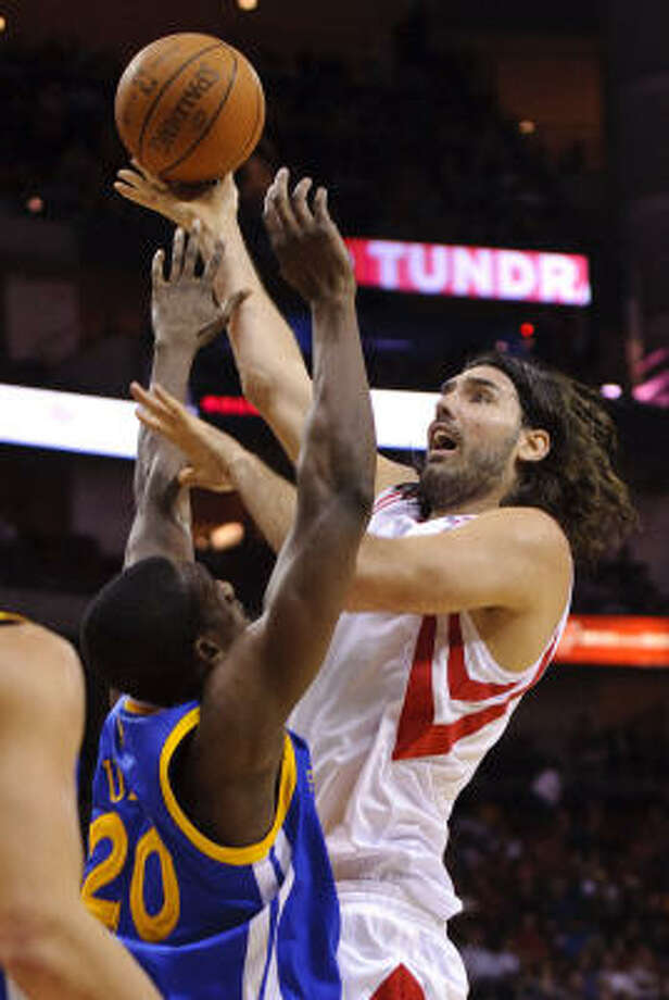 Rockets forward Luis Scola (4) drives against Warriors' Ekpe Udoh (20). Photo: Dave Einsel, AP
