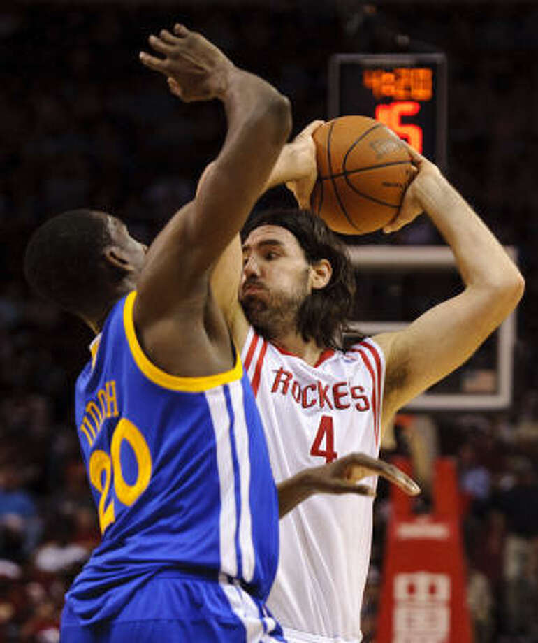 Rockets forward Luis Scola (4) tries to pass the ball around Warriors' Ekpe Udoh (20). Photo: Dave Einsel, AP