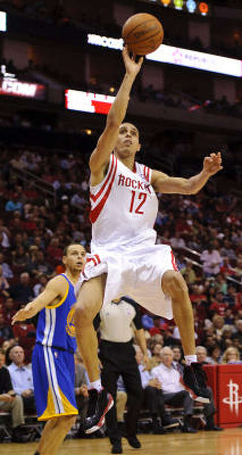 Rockets shooting Kevin Martin (12) drives past Warriors' Stephen Curry, left. Photo: Dave Einsel, AP