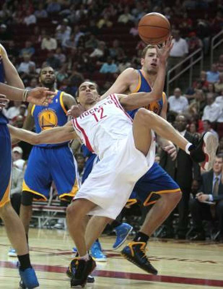Rockets guard Kevin Martin (12) is taken down by Warriors forward David Lee (10). Photo: Billy Smith II, Chronicle