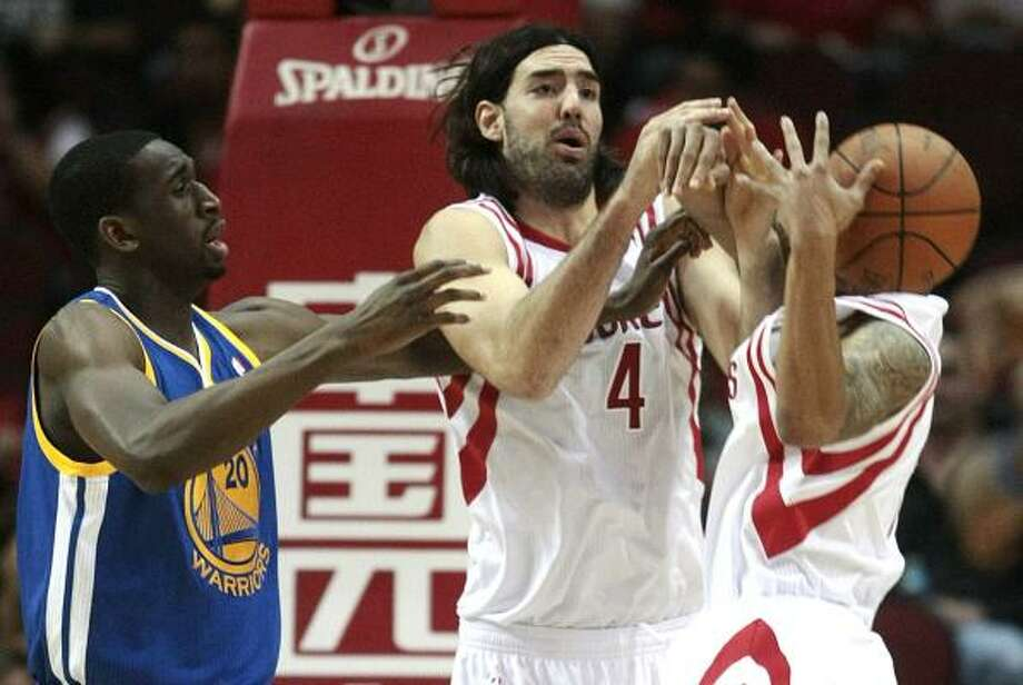 Warriors center Ekpe Udoh, left, fights for a rebound with Rockets forward Luis Scola (4) and guard Courtney Lee (5). Photo: Billy Smith II, Chronicle