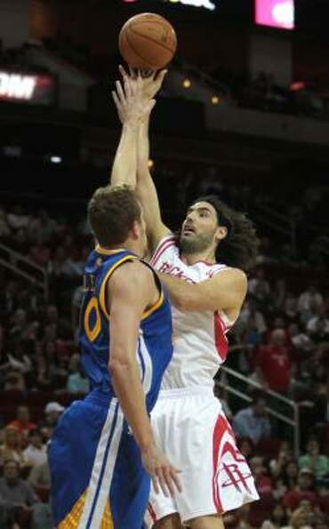 Rockets forward Luis Scola (4) puts a shot up over Warriors forward David Lee (10).