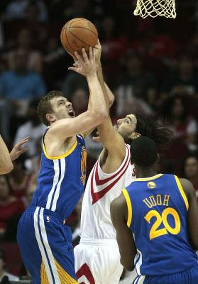 Warriors forward David Lee (10) goes up for a shot while Rockets forward Luis Scola (4) defends. Photo: Billy Smith II, Chronicle