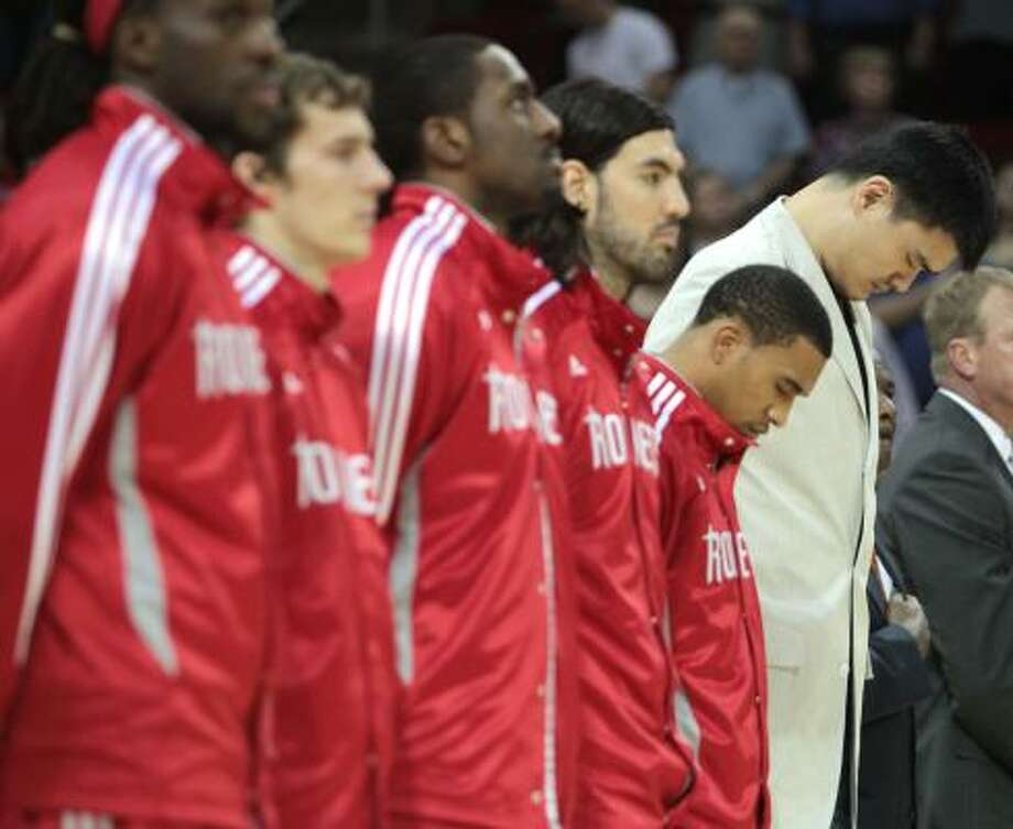 Rockets center Yao Ming, far right, stands with his teammates during the national anthem before the start of the game. Photo: Billy Smith II, Chronicle