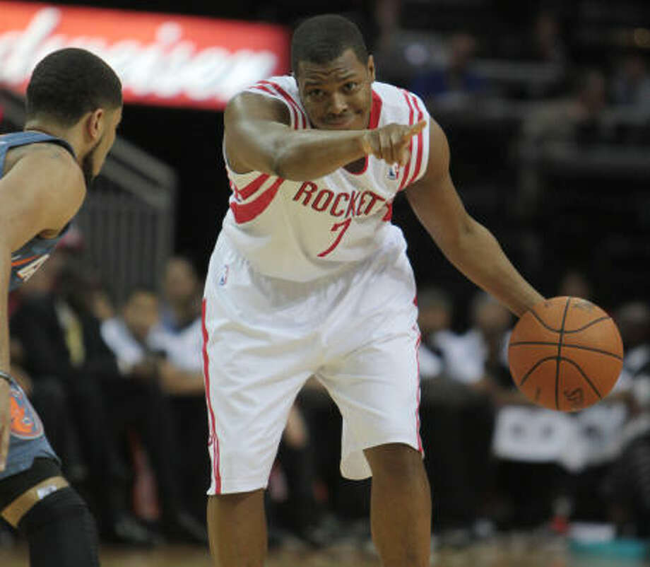 March 16: Rockets 94, Bobcats 78 Rockets guard Kyle Lowry directs the offense while approaching Bobcats guard D.J. Augustin in the first half. Lowry finished with 11 points, nine rebounds and six assists. Photo: Billy Smith II, Chronicle