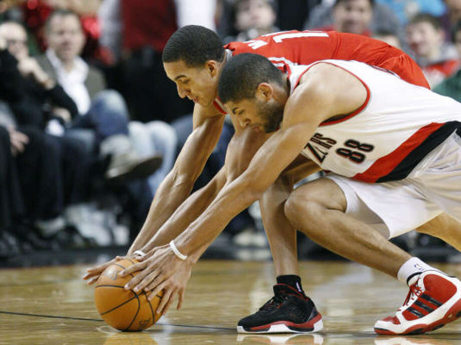 Rockets guard Kevin Martin and Trail Blazers forward Nicolas Batum dive for a loose ball in the third quarter. Martin scored 20 points as the Rockets won their fifth straight game. Photo: Rick Bowmer, AP