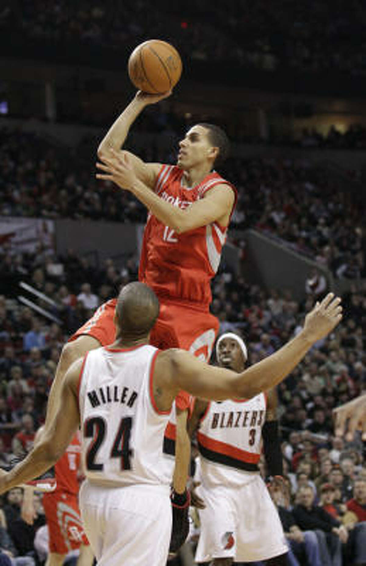 Rockets guard Kevin Martin puts up a shot as Trail Blazers guard Andre Miller (24) and Gerald Wallace look on in the second quarter.