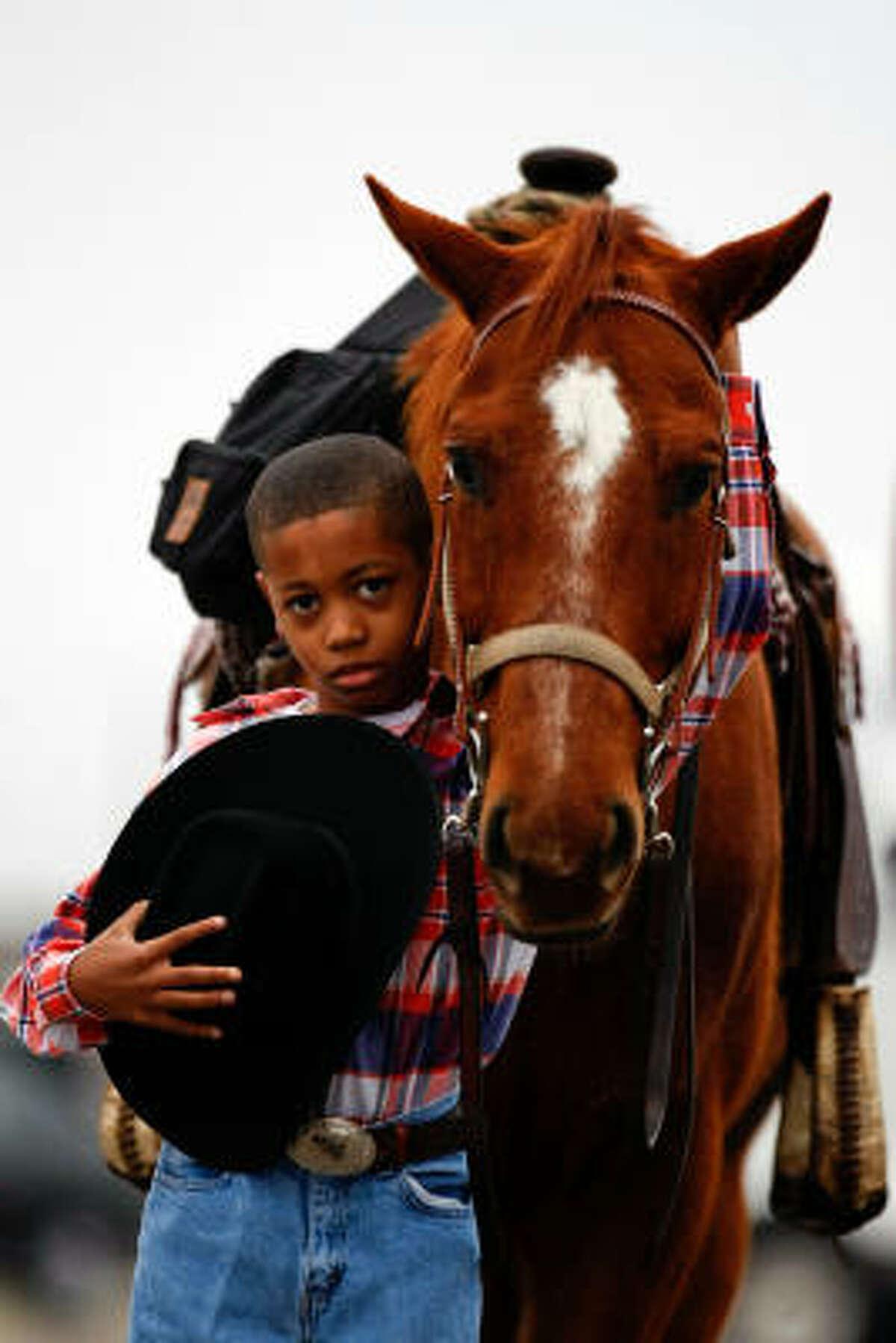 Jordan McClellan, 8, of Houston, holds onto a horse named Starburst before leaving the Fort Bend County Fairgrounds in Rosenberg to join the Southwest Trail Ride Association.