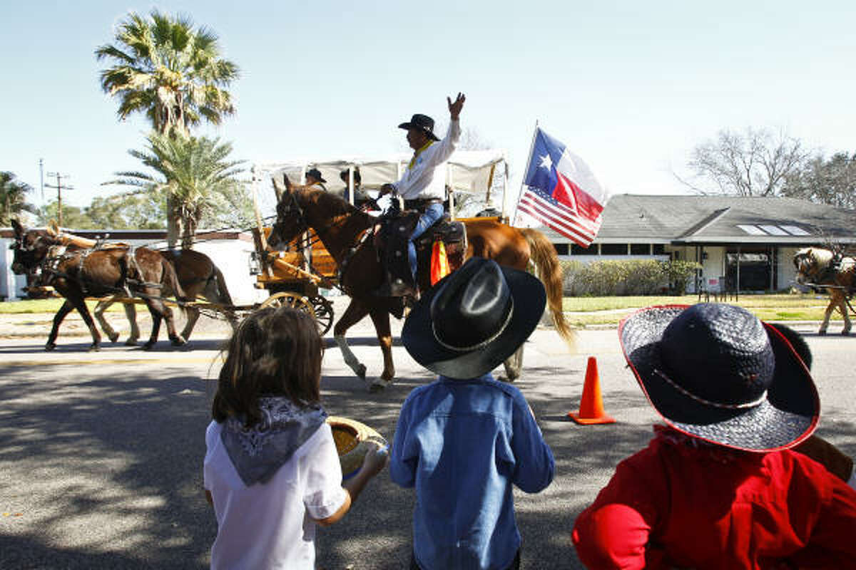 A cowboy with the Southwestern Trail Riders waves to students at Kolter Elementary in the Bellaire neighborhood while making their way to Memorial Park.