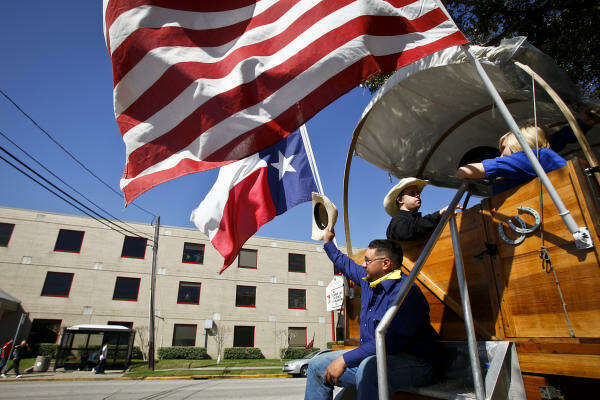 David Ramirez waves his hat as he and other trail riders from the Los Vaqueros group make their way past Bellaire High School.