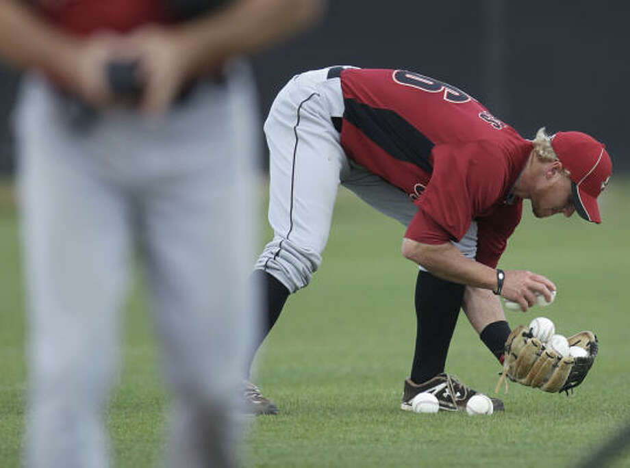 Astros catcher J.R. Towles picks up balls for a drill. Photo: Karen Warren, Chronicle