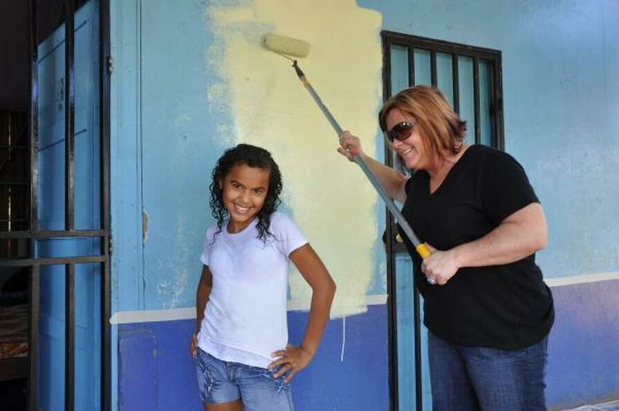 Carmela, 12, strikes a pose as Jen Grant gives her school in Costa Rica a fresh coat of paint.