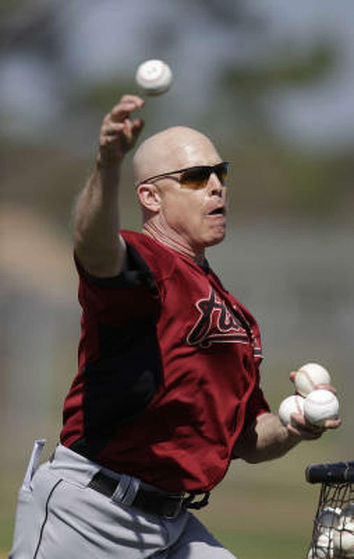 Astros manager Brad Mills throws batting practice.