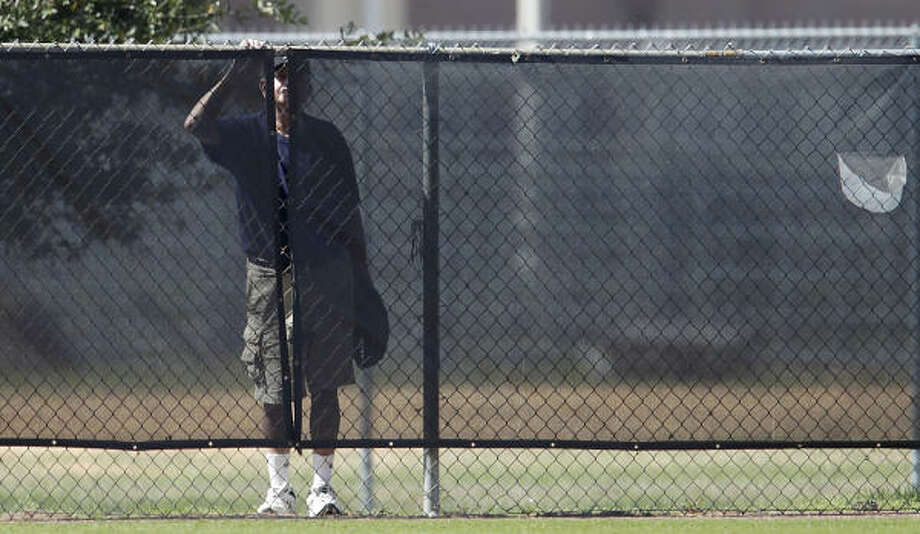 A fan peeks through the mesh of the outfield fence of Field 3 as he waits to see whether someone will hit a home run. Photo: Karen Warren, Chronicle