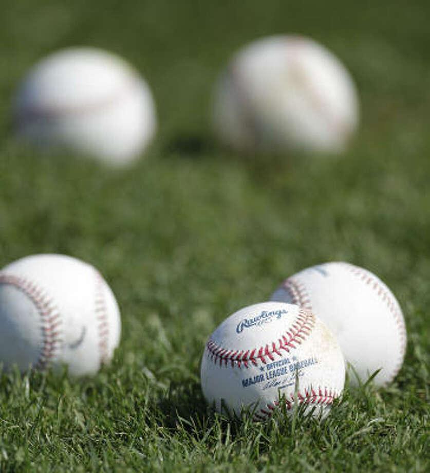 Baseballs sit on the field, ready for use. Photo: Karen Warren, Chronicle