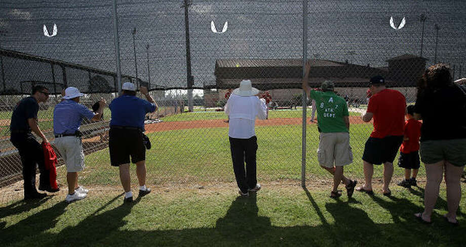 Fans peek through the fence to watch catchers and pitchers warm up. Photo: Karen Warren, Chronicle