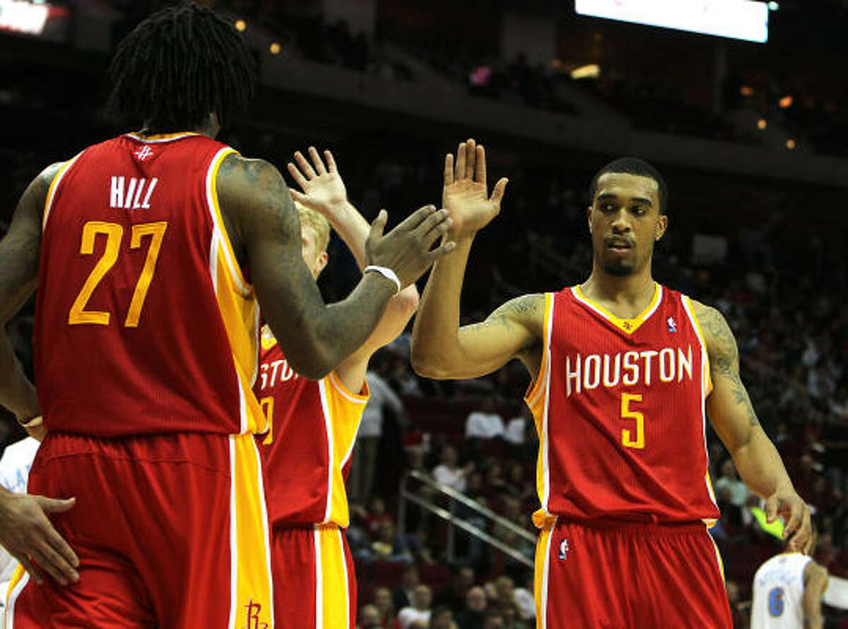 Rockets guard Courtney Lee, right, high-fives teammate Jordan Hill, left, as the Rockets play the Nuggets during the fourth quarter.
