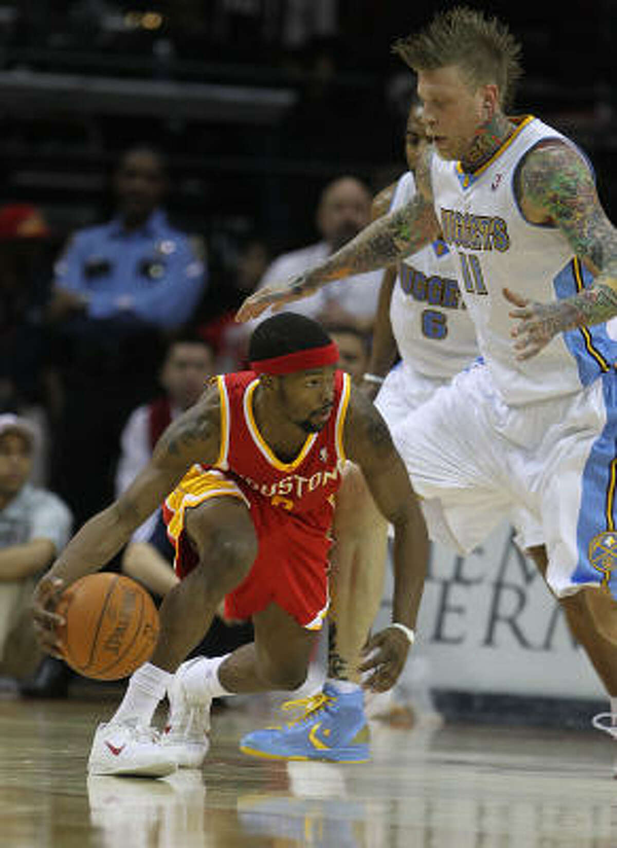 Rockets point guard Aaron Brooks, left, tries to dribble around Nuggets forward Chris Andersen.