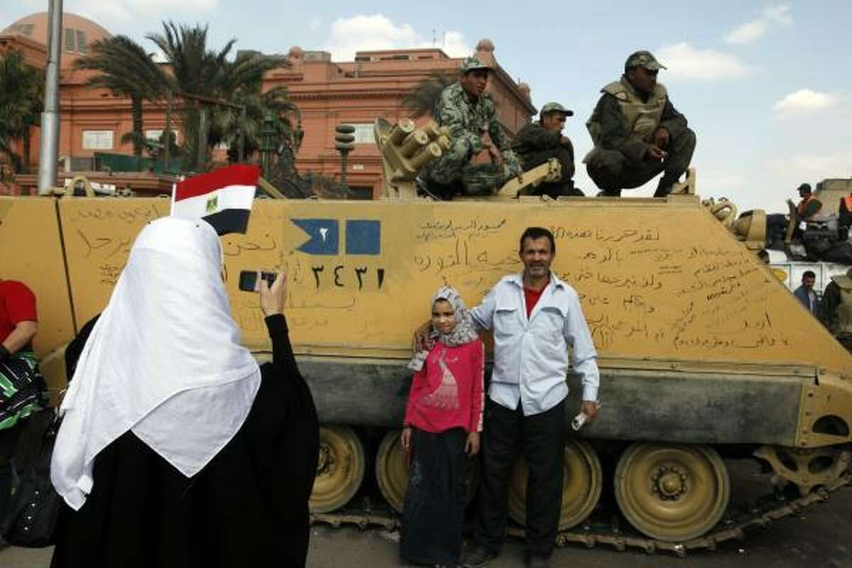 Egyptians pose for family photo in front of an army armored vehicle at Tahrir Square in Cairo, Egypt, Saturday, Feb. 12, 2011. Egypt exploded with joy, tears, and relief after pro-democracy protesters brought down President Hosni Mubarak with a momentous march on his palaces and state TV. Mubarak, who until the end seemed unable to grasp the depth of resentment over his three decades of authoritarian rule, finally resigned Friday and handed power to the military.