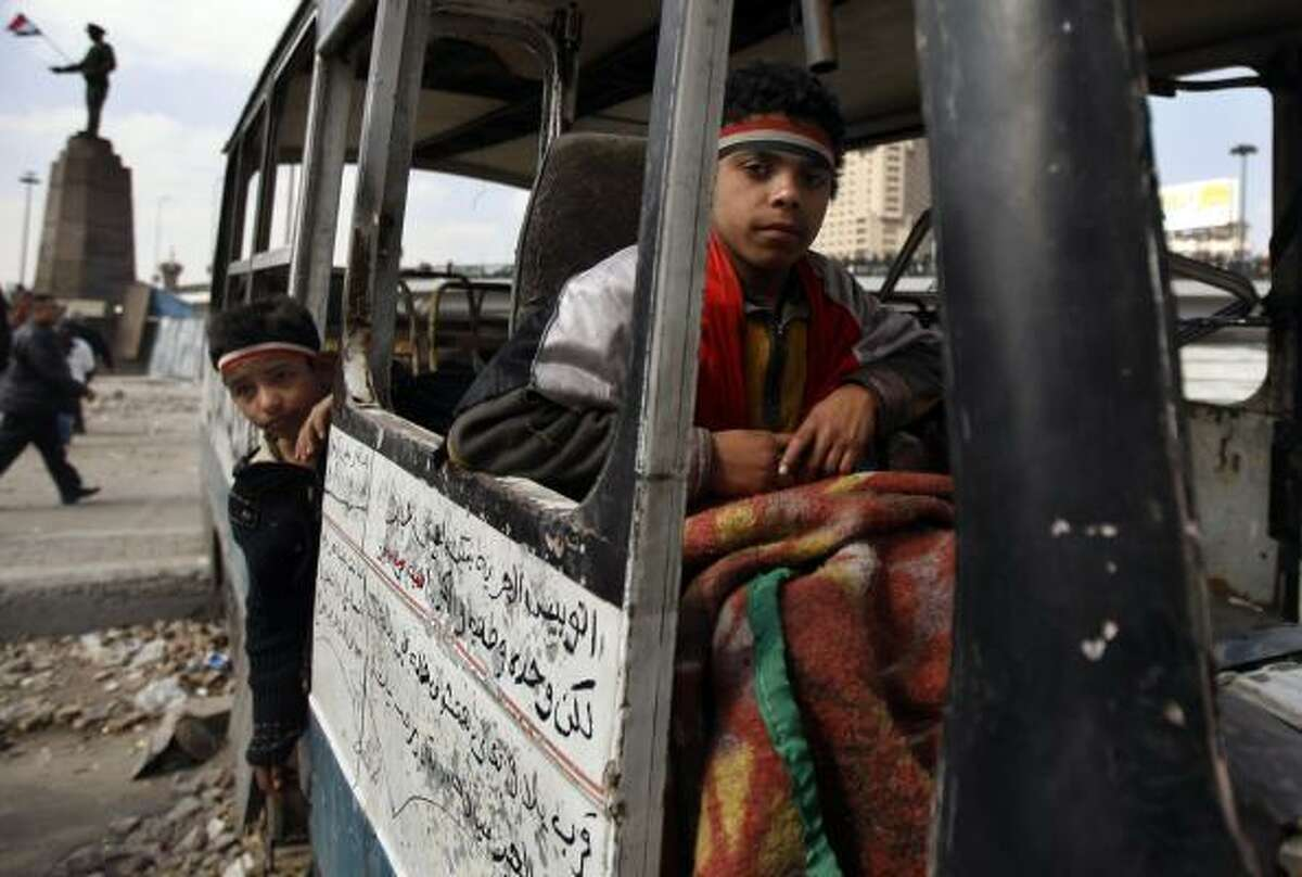 Young anti-government demonstrators sit in destroyed vehicle, on a street near Tahrir Square in Cairo, Egypt.
