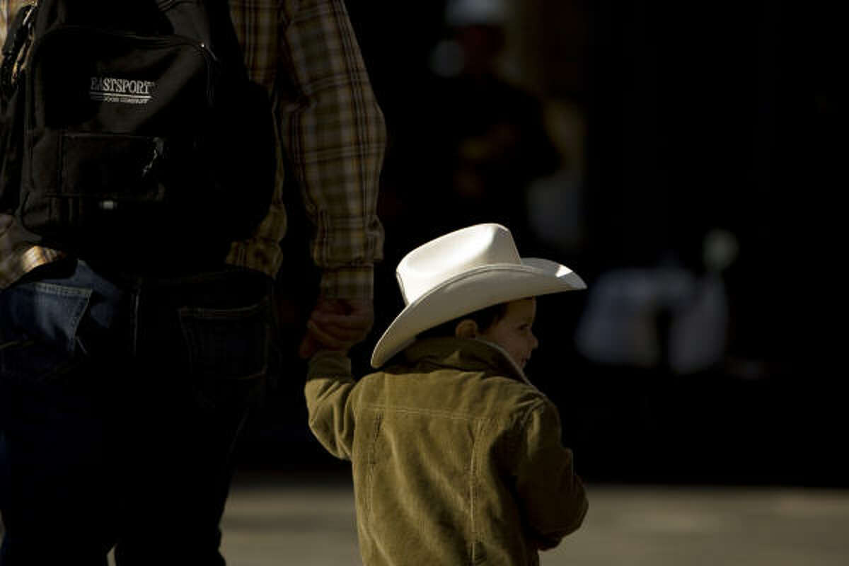 Omar Narvaez, 2, of Houston walks with his father, Waldo Narvaez, to watch the 72nd annual Downtown Rodeo Parade.