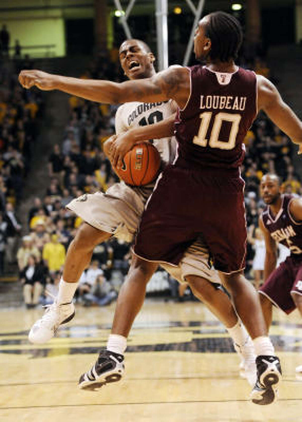 Colorado guard Alec Burks, left, is fouled by Texas A&M forward David Loubeau during the second half. Burks scored a game-high 24 points in a losing effort.