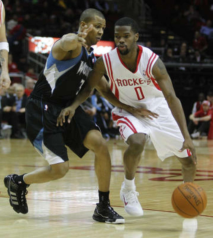 Rockets guard Aaron Brooks, right, looks to get past Timberwolves guard Sebastian Telfair, left, during second quarter.