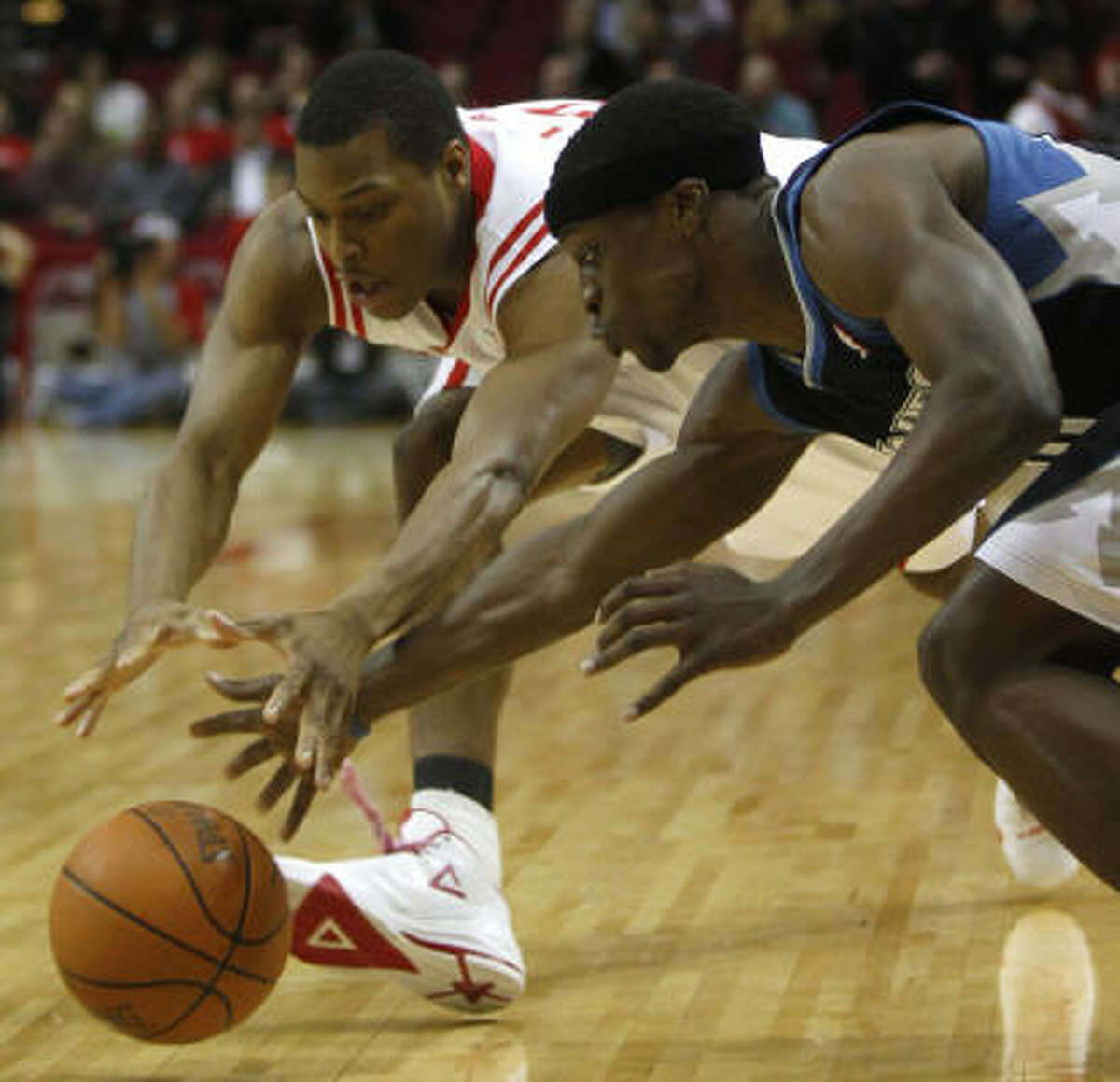 Rockets guard Kyle Lowry, left, and Timberwolves guard Jonny Flynn, right, scramble for a loose ball during first quarter.