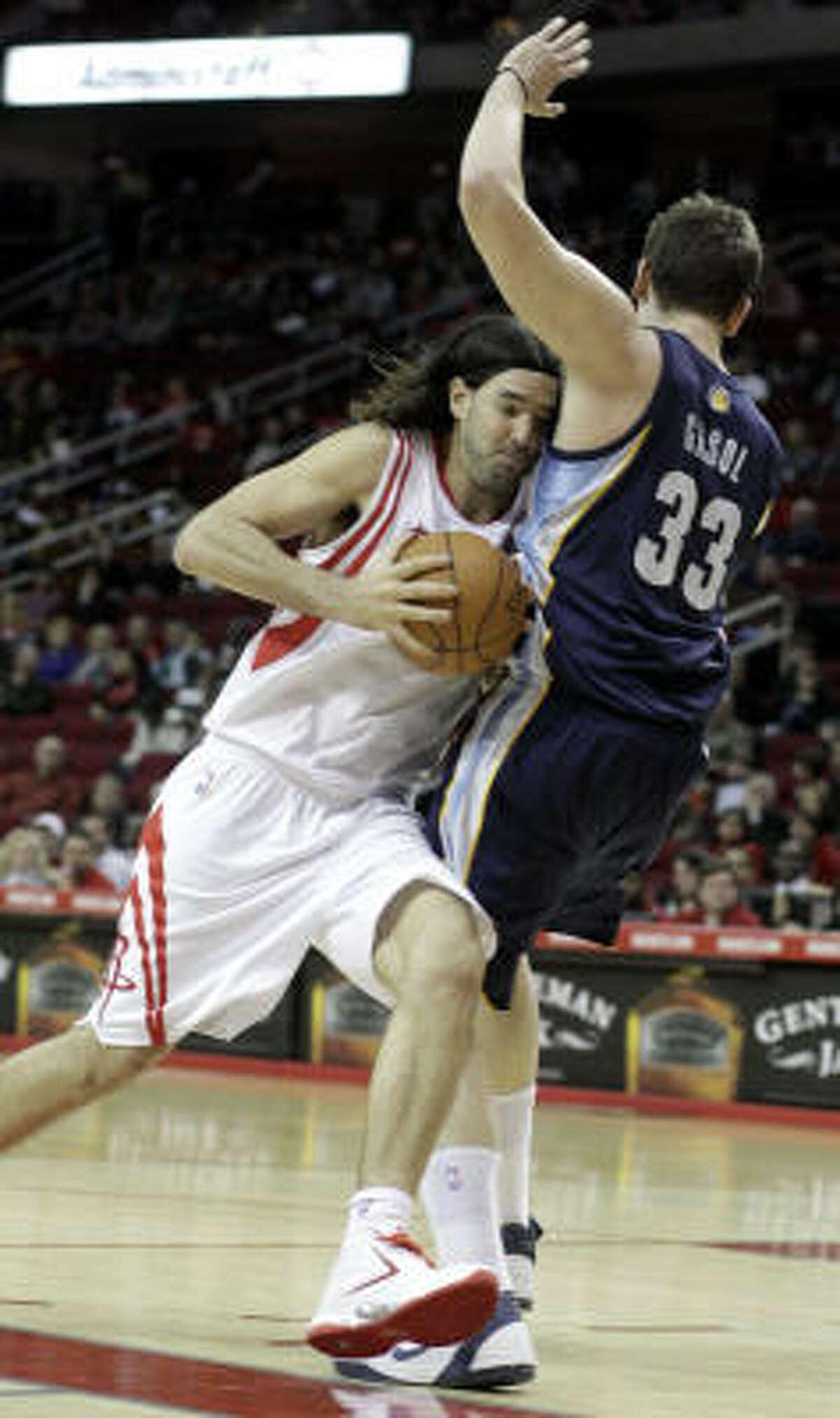 Rockets forward Luis Scola, left, drives into Grizzlies center Marc Gasol (33).
