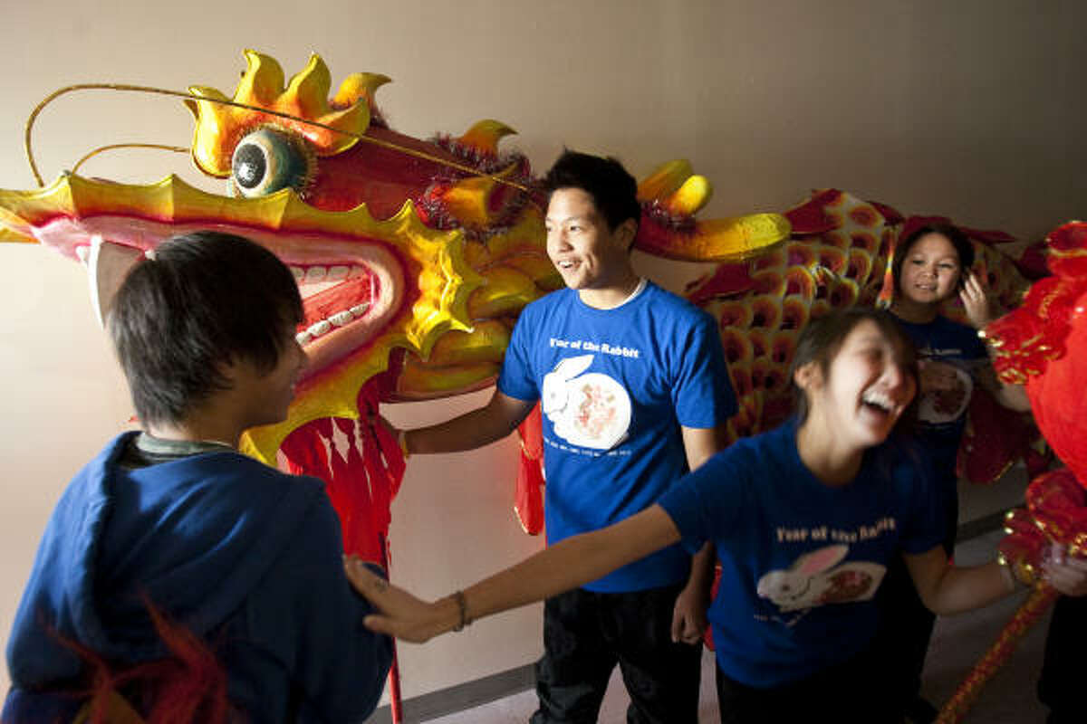 Alex Tso, 15, of Houston holds up the Chinese New Year Dragon's head as Kelly Wang, 17, of Houston, teases Josh Fan, 15, of Sugar land during the 2011 Lunar New Year Festival. Tso performed the dragon dance with other dancers. The dragon is a symbol of power, strength, and good luck.